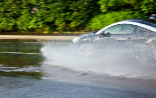 Flooded Car Driving Through Puddle