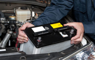 Auto Mechanic Replacing a Car Battery, Northwest Auto Center of Houston